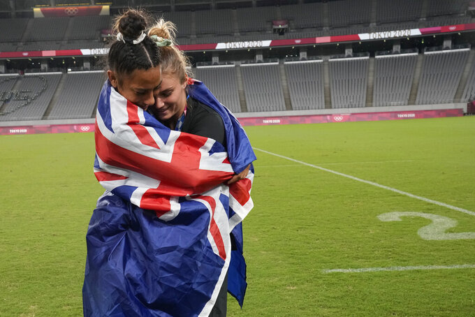 New Zealand's Risi Pouri-Lane, left, and Michaela Blyde hug, wrapped in a national flag, as they celebrate in the empty stadium after receiving their gold medals in women's rugby sevens at the 2020 Summer Olympics, Saturday, July 31, 2021 in Tokyo, Japan. (AP Photo/Shuji Kajiyama)