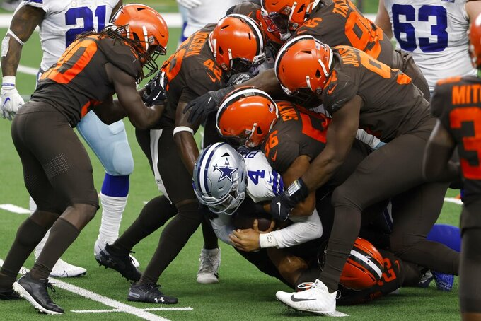A group of Cleveland Browns defenders stop Dallas Cowboys quarterback Dak Prescott (4) after a short run in the second half of an NFL football game in Arlington, Texas, Sunday, Oct. 4, 2020. (AP Photo/Ron Jenkins)