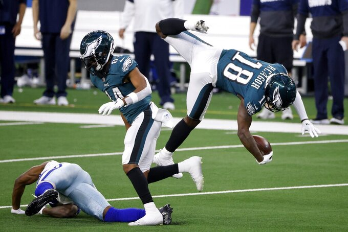 Philadelphia Eagles wide receiver Jalen Reagor (18) is upended by a Dallas Cowboys defender after catching a pass in the first half of an NFL football game in Arlington, Texas, Sunday, Dec. 27. 2020. (AP Photo/Michael Ainsworth)