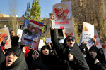 Protesters chant slogans while holding up posters of Gen. Qassem Soleimani during a demonstration in front of the British Embassy in Tehran, Iran, Sunday, Jan. 12, 2020. A candlelight ceremony late Saturday in Tehran turned into a protest, with hundreds of people chanting against the country's leaders — including Supreme Leader Ayatollah Ali Khamenei — and police dispersing them with tear gas. Police briefly detained the British ambassador to Iran, Rob Macaire, who said he went to the Saturday vigil without knowing it would turn into a protest. (AP Photo/Ebrahim Noroozi)