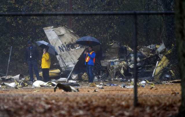 FILE - In this Thursday, Dec. 20, 2018, file photo, investigators work the scene of a small plane crash in a city park which killed all four people on board, in northwest Atlanta. The National Transportation Safety Board says in a report that Tennessee businessman Wei Chen, who was flying the plane, likely lost control after becoming disoriented in cloudy weather after taking off. (AP Photo/John Amis, File)