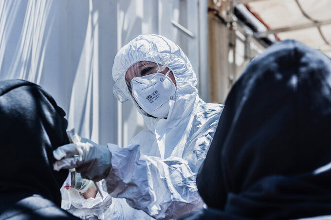 """A medical staffer conducts COVID-19 tests aboard the Ocean Viking ship in the Mediterranean Sea, Sunday, July 5, 2020. A humanitarian group says its rescue ship with 180 migrants stranded aboard for days has """"finally"""" received instructions to sail to an Italian port, so its passengers can be disembarked. SOS Mediterranee in a tweet on Sunday also described """"relief on the #Ocean Viking"""" when the ship's crew and passengers learned that the rescued migrants are to be disembarked at Porto Empedocle, Sicily, the next day. (Flavio Gasperini/SOS Mediterranee via AP)"""