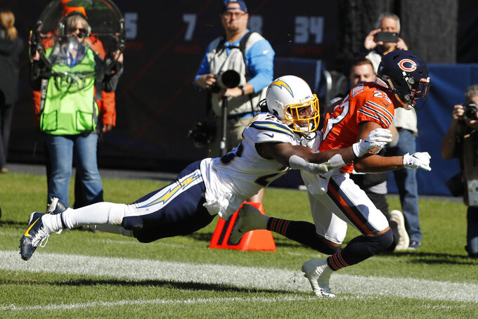 Chicago Bears cornerback Kyle Fuller is tackled by Los Angeles Chargers running back Melvin Gordon (25) after intercepting a pass during the first half of an NFL football game, Sunday, Oct. 27, 2019, in Chicago. (AP Photo/Charles Rex Arbogast)