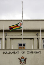 The Zimbabwean flag flies at half-mast at the parliament building in Harare, Zimbabwe, Saturday, Sept. 7, 2019. Former Zimbabwean leader Robert Mugabe, an ex-guerrilla chief who took power when the African country shook off white minority rule and presided for decades while economic turmoil and human rights violations eroded its early promise, has died in Singapore. He was 95. (AP Photo/Themba Hadebe)