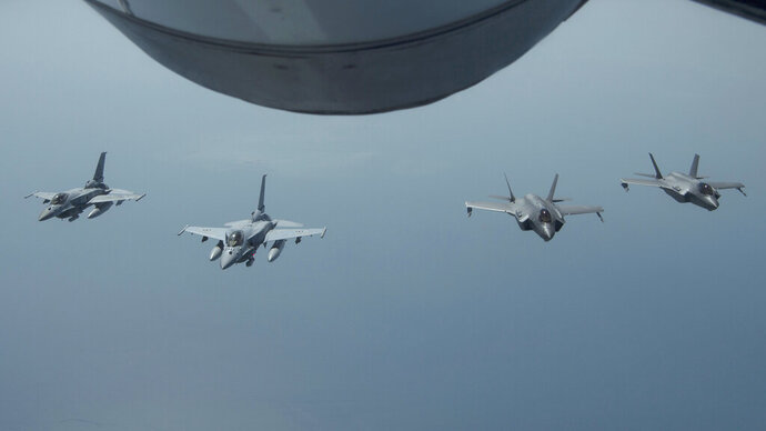 FILE - In this May 29, 2019 file photo released by the U.S. Air Force, United Arab Emirates Air Force Desert Falcons fly in formation with U.S. F-35A Lightning IIs in an undisclosed location in Southwest Asia. Tensions between the United States and Iran have soared in recent weeks, with Washington dispatching warships and bombers around the Persian Gulf, and Tehran threatening to resume higher uranium enrichment. The tensions come a year after President Donald Trump withdrew from Iran's 2015 nuclear accord with world powers and restored crippling sanctions. (Staff Sgt. Chris Drzazgowski/U.S. Air Force via AP, File)
