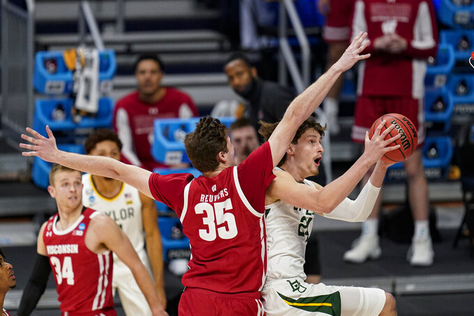 Baylor guard Matthew Mayer (24) shoots under Wisconsin forward Nate Reuvers (35) in the first half of a second-round game in the NCAA men's college basketball tournament at Hinkle Fieldhouse in Indianapolis, Sunday, March 21, 2021. (AP Photo/Michael Conroy)