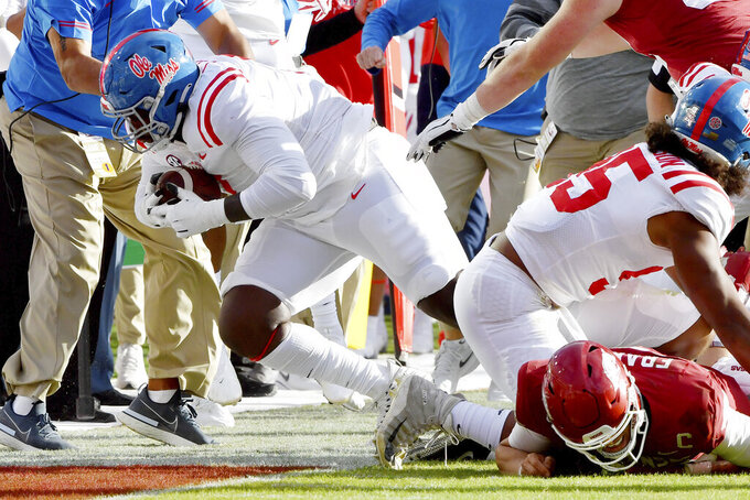 Mississippi defensive lineman LeDarrius Cox, front left, recovers an Arkansas fumble during the second half of an NCAA college football game Saturday, Oct. 17, 2020, in Fayetteville, Ark. (AP Photo/Michael Woods)