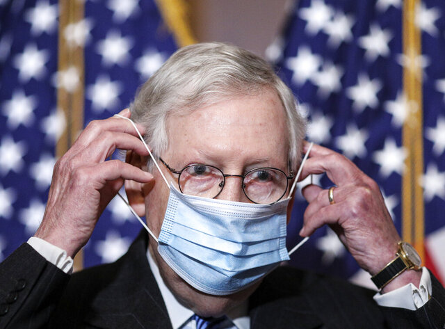 Senate Majority Leader Mitch McConnell of Ky., removes his face mask as he arrives for a news conference with other Senate Republicans on Capitol Hill in Washington, Tuesday, Dec. 15, 2020. (Tom Brenner/Pool via AP)