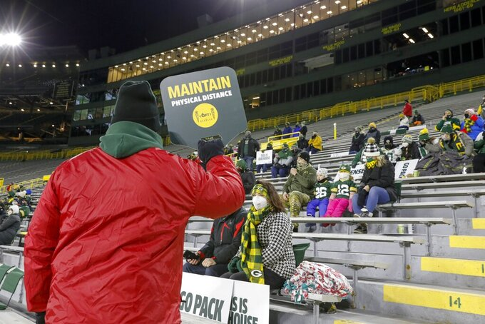 A worker reminds a small croud to maintain tphysical distance during the first half of an NFL football game between the Green Bay Packers and the Chicago Bears Sunday, Nov. 29, 2020, in Green Bay, Wis. (AP Photo/Mike Roemer)