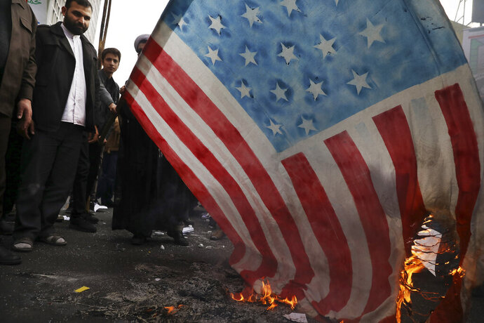 Demonstrators set fire to a rendition of the U.S. flag during a rally in front of the former U.S. Embassy in Tehran, Iran, Monday, Nov. 4, 2019. Reviving decades-old cries of