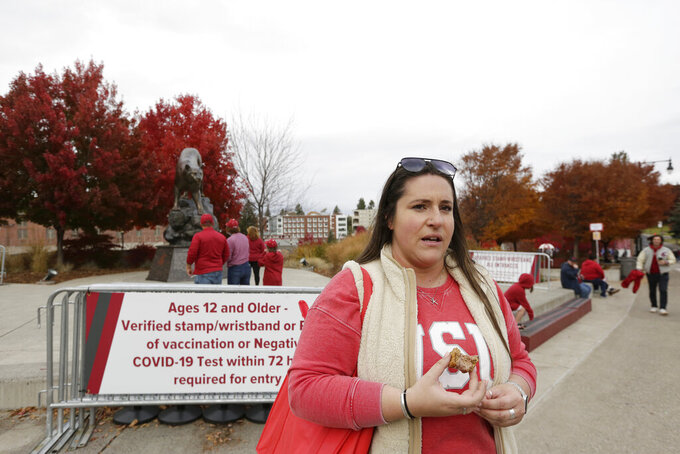 Washington State fan Trisha Griggs talks with The Associated Press about this week's firing of football head coach Nick Rolovich and four assistant coaches for refusing a state mandate that all employees get vaccinated against COVID-19, outside Martin Stadium before an NCAA college football game between Washington State and BYU, Saturday, Oct. 23, 2021, in Pullman, Wash. (AP Photo/Young Kwak)