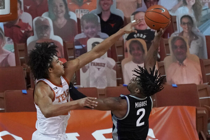 Texas' Jericho Sims, left, blocks a shot by Kansas State's Selton Miguel, right, during the first half of an NCAA college basketball game in Austin, Texas, Saturday, Jan. 16, 2021. (AP Photo/Chuck Burton)
