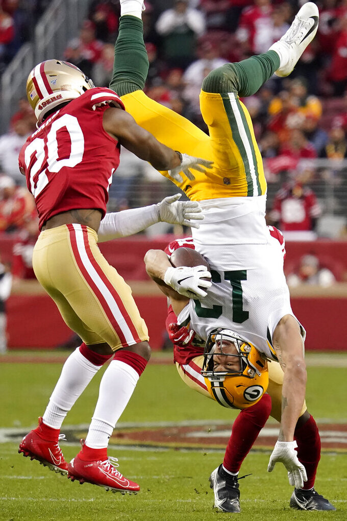 Green Bay Packers wide receiver Allen Lazard (13) falls to the ground between San Francisco 49ers free safety Jimmie Ward (20) and Emmanuel Moseley during the first half of the NFL NFC Championship football game Sunday, Jan. 19, 2020, in Santa Clara, Calif. (AP Photo/Tony Avelar)
