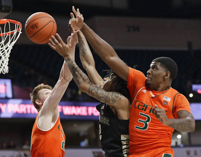 Wake Forest's Sharone Wright Jr., center, tries to shoot between Miami's Anthony Lawrence II, right, and Sam Waardenburg, left, during the first half of an NCAA college basketball game in Winston-Salem N.C., Tuesday, Feb. 26, 2019. (AP Photo/Chuck Burton)