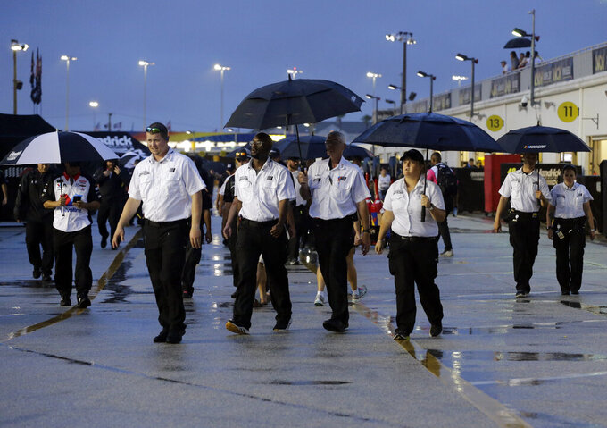 NASCAR officials leave the garage area after the Cup Series auto race was postponed because of inclement weather at Daytona International Speedway, Saturday, July 6, 2019, in Daytona Beach, Fla. The race was rescheduled for Sunday. (AP Photo/Terry Renna)