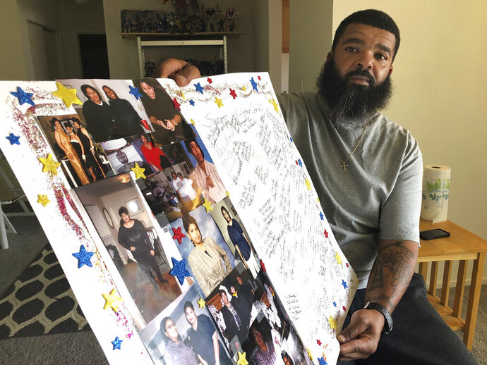 Roland Mack holds a poster with pictures and messages made by family members in memory of his sister, Chantee Mack, in District Heights, Md., on Friday, June 19, 2020. The Prince George's County, Md., public health worker died of COVID-19 after, family and co-workers believe, she and several colleagues contracted the disease in their office. (AP Photo/Federica Narancio)
