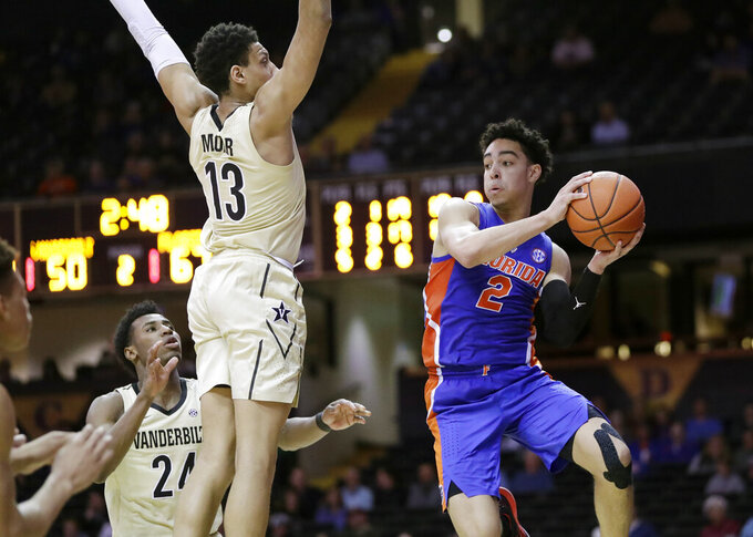 Florida guard Andrew Nembhard (2) passes the ball around Vanderbilt's Matthew Moyer (13) and Aaron Nesmith (24) during the second half of an NCAA college basketball game Wednesday, Feb. 27, 2019, in Nashville, Tenn. (AP Photo/Mark Humphrey)