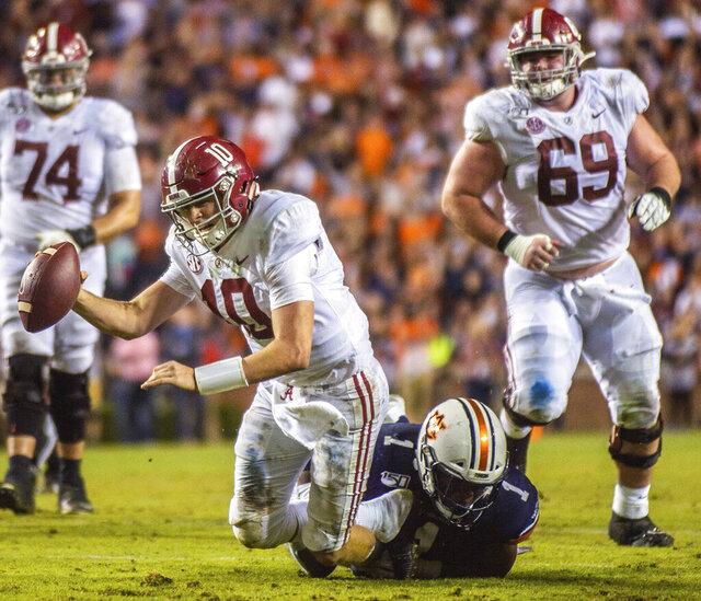 Alabama quarterback Mac Jones (10) is sacked by Auburn defensive end Big Kat Bryant (1) during the second half of an NCAA college football game Saturday, Nov. 30, 2019, in Auburn, Ala. (Dan Busey/The Decatur Daily via AP)