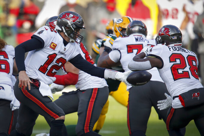 Tampa Bay Buccaneers quarterback Tom Brady (12) hands off to Leonard Fournette (28) during the first half of the NFC championship NFL football game against the Green Bay Packers in Green Bay, Wis., Sunday, Jan. 24, 2021. (AP Photo/Matt Ludtke)