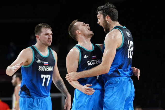 Slovenia's Mike Tobey (10) celebrates a score against Spain with teammates Klemen Prepelic (7) and Luka Doncic (77) during a men's basketball preliminary round game at the 2020 Summer Olympics, Sunday, Aug. 1, 2021, in Saitama, Japan. (AP Photo/Eric Gay)