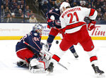 Columbus Blue Jackets' Elvis Merzlikins, left, of Latvia, makes a save against Carolina Hurricanes' Nino Niederreiter, of Switzerland, during the first period of an NHL hockey game Thursday, Jan. 16, 2020, in Columbus, Ohio. (AP Photo/Jay LaPrete)
