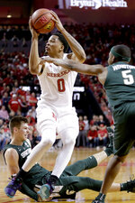 Nebraska's James Palmer Jr. (0) shoots between Michigan State's Matt McQuaid, bottom, and Cassius Winston (5) during the first half of an NCAA college basketball game in Lincoln, Neb., Thursday, Jan. 17, 2019. (AP Photo/Nati Harnik)