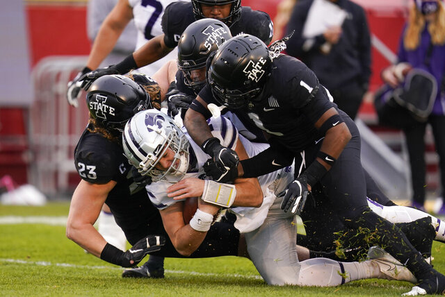 Kansas State quarterback Will Howard, center, is tackled by Iowa State defenders Mike Rose (23) and Isheem Young (1) during the first half of an NCAA college football game, Saturday, Nov. 21, 2020, in Ames, Iowa. (AP Photo/Charlie Neibergall)