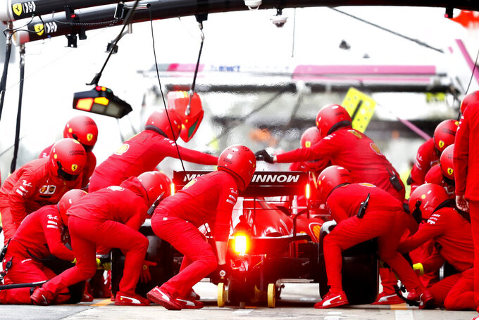 Pit crew work on the car of Ferrari driver Charles Leclerc of Monaco as he pulls into the pits during the Formula One pre-season testing session at the Barcelona Catalunya racetrack in Montmelo, outside Barcelona, Spain, Friday, Feb. 28, 2020. (AP Photo/Joan Monfort)