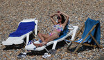 A Beachgoer enjoy the sunshine and sea on what is now Britain's hottest day of the year so far, in Brighton, England, Friday, July 31, 2020. Temperatures have reached 35C (95F) at London's Heathrow Airport. (AP Photo/Alastair Grant)