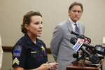 Tulsa Police Sgt. Jillian Phippen speaks during a news conference, Thursday, Sept. 12, 2019, in Oklahoma City, to announce that Oklahoma Attorney General Mike Hunter, right, is sending cease-and-desist letters to two companies that are marketing do-it-yourself sexual assault kits victims can use to gather evidence at home. (AP Photo/Sue Ogrocki)