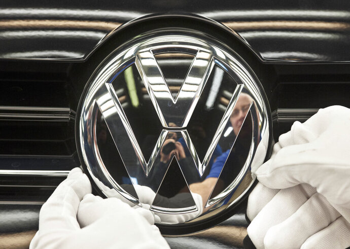 FILE - In this Nov. 9, 2012 file picture a worker fixes a sign at a Volkswagen Golf car during a press tour in Zwickau, central Germany. Automaker Volkswagen is raising the bar for its plunge into battery powered cars, saying it will reach its goal of 1 million e-autos per year two years earlier than planned. (AP Photo/Jens Meyer,File)