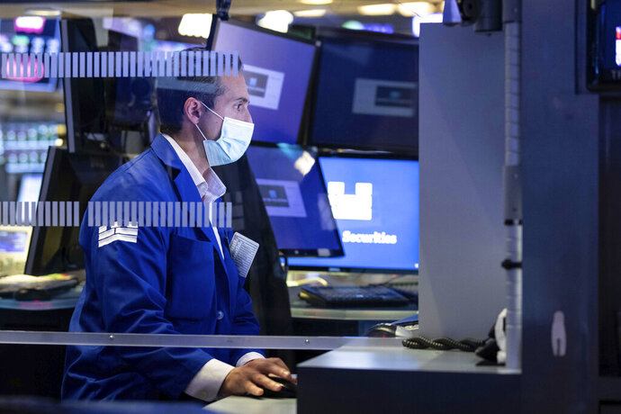 In this photo provided by the New York Stock Exchange, a specialist works at his post on the trading floor, Monday Nov. 30, 2020, in New York.  Companies in the S&P 500 reported that their earnings held up surprising well in the third-quarter despite an economy still struggling to recover from the virus pandemic. (Nicole Pereira/New York Stock Exchange via AP, File)