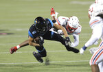 Liberty safety Javon Scruggs (1) tackles Coastal Carolina wide receiver Jaivon Heiligh (6) during the second half of the Cure Bowl NCAA college football game Saturday, Dec. 26, 2020, in Orlando, Fla. (AP Photo/Matt Stamey)