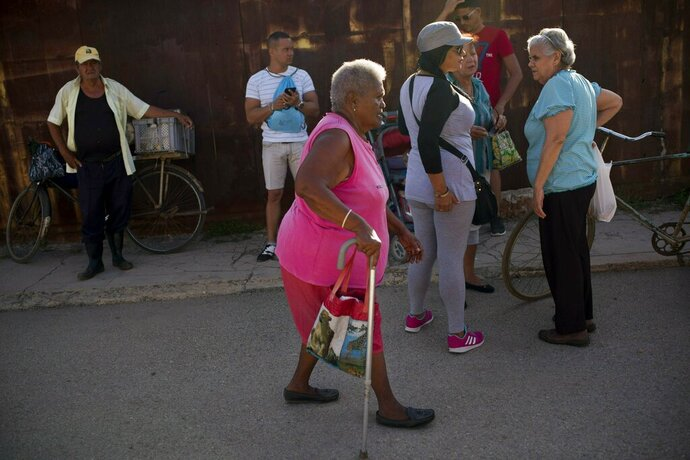 Pura Castell walks to a government-run butcher shop to buy chicken, after failing to find chicken the previous day in Bauta, Cuba, Friday, April 12, 2019. A neighbor informed her that chicken had arrived at the government store that distributes almost free monthly food rations. (AP Photo/Ramon Espinosa)