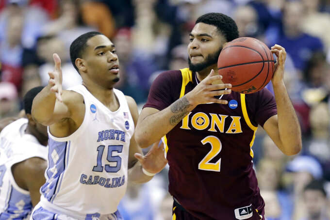 Iona's E.J. Crawford (2) looks to pass against North Carolina's Garrison Brooks (15) in the first half during a first round men's college basketball game in the NCAA Tournament in Columbus, Ohio, Friday, March 22, 2019. (AP Photo/Tony Dejak)