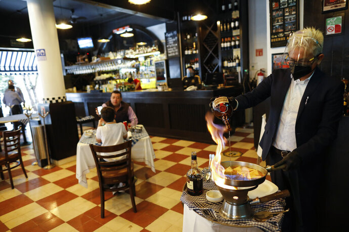 A waiter prepares an order of crepes Suzette inside Argentine grill Quebracho, in the Cuauhtemoc neighborhood of Mexico City, Monday, Jan. 11, 2021. More than three weeks into Mexico City's second pandemic shutdown some restaurateurs worried about their ability to survive ignored official warnings and opened limited seating Monday under the slogan,
