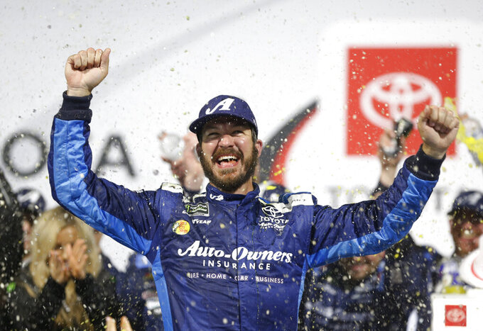 Martin Truex Jr. (19) celebrates winning the NASCAR Cup series auto race at Richmond Raceway in Richmond, Va., Saturday, April 13, 2019. (AP Photo/Steve Helber)