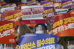 A doctor holds up a placard during a rally against the government medical policy in Seoul, South Korea, Friday, Aug. 14, 2020. Thousands of doctors in South Korea began a strike Friday in protest of government medical policy, causing concerns about treatment of patients amid the coronavirus pandemic. The signs read: