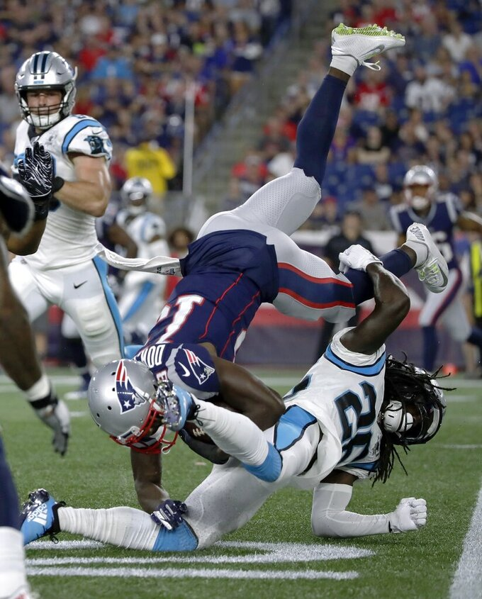 Carolina Panthers cornerback Donte Jackson, below, upends New England Patriots wide receiver Phillip Dorsett in the first quarter of an NFL preseason football game, Thursday, Aug. 22, 2019, in Foxborough, Mass. (AP Photo/Elise Amendola)