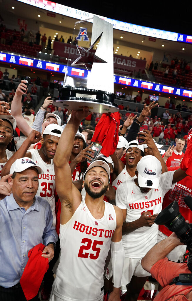 Houston's Galen Robinson Jr. (25) holds up the trophy after Houston beat SMU in an NCAA college basketball game Thursday, March 7, 2019, in Houston. Houston won 90-79 to clinch a share of the American Athletic Conference Championship. (AP Photo/David J. Phillip)