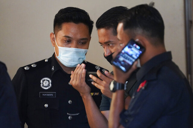 Police officials view the livestream of the court case of French-Irish teen, Nora Anne Quoirin at the court in Seremban, Negeri Sembilan state, Monday, Aug. 24, 2020. A Malaysian coroner began an inquest Monday into the death of Quoirin,  a year after her naked body was found near a nature resort where she mysteriously vanished while on holiday. (AP Photo/Vincent Thian)