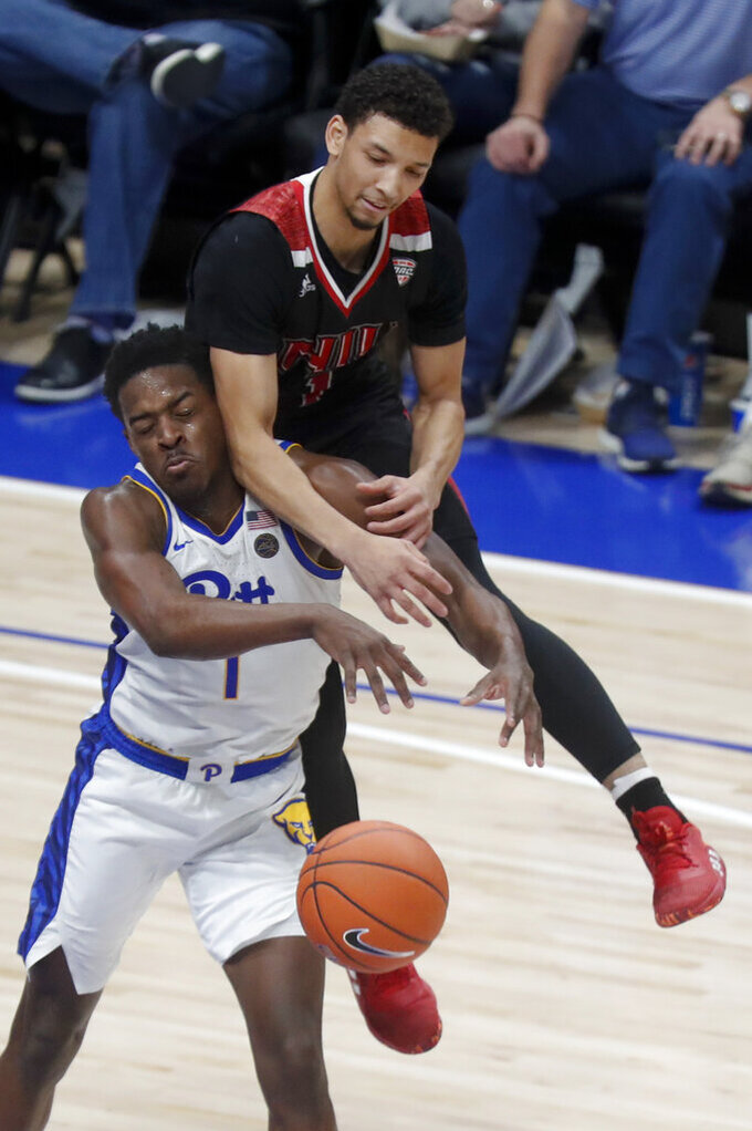 Northern Illinois's Trendon Hankerson, top, jumps on Pittsburgh's Xavier Johnson as he tries for the ball during the second half of an NCAA college basketball game, Monday, Dec. 16, 2019, in Pittsburgh. Pittsburgh won 59-50. (AP Photo/Keith Srakocic)