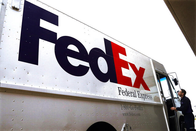 FILE - In this Dec. 18, 2014 file photo, a Federal Express driver returns to his truck after delivering a package to a business in Springfield, Ill. FedEx earned $1.25 billion in its latest quarter, as online shopping remained popular among customers avoiding stores and shipments between businesses improved. The delivery giant reported Tuesday, Sept. 15, 2020 that it brought in $19.3 billion in revenue during the three months that ended Aug. 31, FedEx's fiscal first quarter. (AP Photo/Seth Perlman, File)