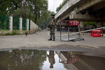 Indian paramilitary soldier stands guard near a temporary checkpoint on the road leading towards Independence Day parade venue during lockdown in Srinagar, Indian controlled Kashmir, Thursday, Aug. 15, 2019. Indian Prime Minister Narendra Modi says that stripping the disputed Kashmir region of its statehood and special constitutional provisions has helped unify the country. Modi gave the annual Independence Day address from the historic Red Fort in New Delhi as an unprecedented security lockdown kept people in Indian-administered Kashmir indoors for an eleventh day. (AP Photo/ Dar Yasin)