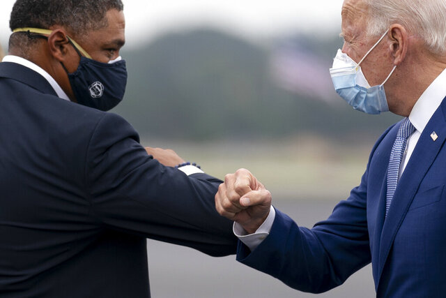 Democratic presidential candidate former Vice President Joe Biden greets Rep. Cedric Richmond, D-La., left, as he arrives at Columbus Airport in Columbus, Ga., Tuesday, Oct. 27, 2020, to travel to Warm Springs, Ga. for a rally. (AP Photo/Andrew Harnik)