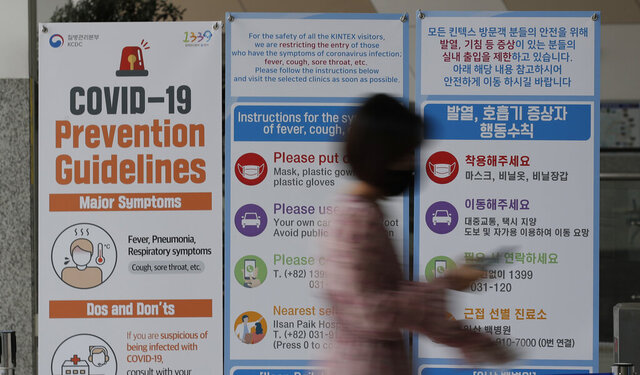 A woman wearing a face mask walks near a banner showing precautions against the new coronavirus at an exhibition and convention center in Goyang, South Korea, Friday, June 12, 2020. (AP Photo/Lee Jin-man)