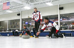 In this Jan. 3, 2019 photo, former Minnesota Vikings football player Jared Allen, right, practices with his curling team for a competition as coach and former Olympian John Benton watches in Blaine, Minn. Allen retired from the NFL in 2015 and wasn't ready to give up on the competition he'd come to enjoy as a five-time All-Pro in a 12-year career. His solution: Make it to the 2022 Olympics _ in curling. Less than a year later, he and three other former NFL players who have never curled before will attempt to qualify for the U.S. championships against curlers who have been throwing stones for most of their lives. (AP Photo/Jim Mone)