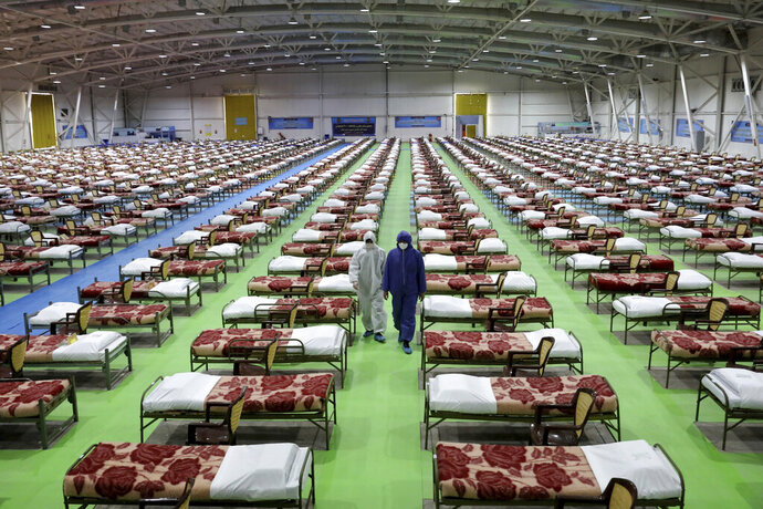 People in protective clothing walk past rows of beds at a temporary 2,000-bed hospital for COVID-19 coronavirus patients set up by the Iranian army at the international exhibition center in northern Tehran, Iran, on Thursday, March 26, 2020. (AP Photo/Ebrahim Noroozi)