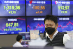 A currency trader watches monitors at the foreign exchange dealing room of the KEB Hana Bank headquarters in Seoul, South Korea, Wednesday, Feb. 26, 2020. Asian shares slid Wednesday following another sharp fall on Wall Street as fears spread that the growing virus outbreak will put the brakes on the global economy.(AP Photo/Ahn Young-joon)