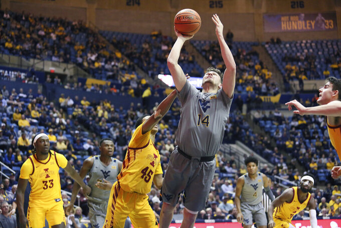 West Virginia guard Chase Harler (14)  shoots as he is defended by Iowa State guard Rasir Bolton (45) during the second half of an NCAA college basketball game Wednesday, Feb. 5, 2020, in Morgantown, W.Va. (AP Photo/Kathleen Batten)